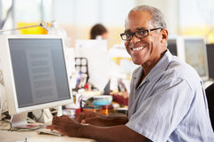 Homem que trabalha na mesa no escritório criativo ocupado imagens de stock
