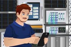 Homem que trabalha na sala do servidor de computador Foto de Stock
