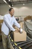Homem que trabalha no armazém de distribuição Fotografia de Stock
