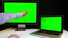 Homem que trabalha no portátil e na exposição com uma tela verde video estoque