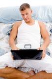 Homem que trabalha no portátil na cama Fotos de Stock Royalty Free