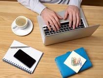Homem que trabalha no portátil na mesa Foto de Stock Royalty Free