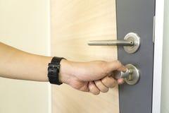 Homem que trava um botão de porta e uns puxadores da porta de aço inoxidável em uma porta de madeira imagem de stock