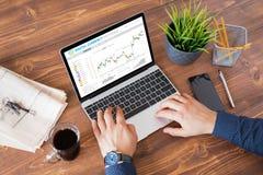 Homem que troca moedas digitais em linha no laptop fotografia de stock royalty free