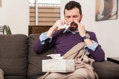 Homem que usa algum pulverizador nasal Fotos de Stock Royalty Free