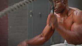 Homem que usa cordas da batalha no gym do crossfit vídeos de arquivo