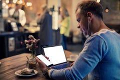 Homem que usa dispositivos da tecnologia no café fotografia de stock royalty free
