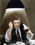 Homem que usa dois telefones (todas as pessoas descritas não são umas vivas mais longo e nenhuma propriedade existe Garantias do  Imagens de Stock