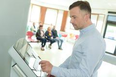 Homem que usa a máquina para registrar a chegada fotografia de stock royalty free