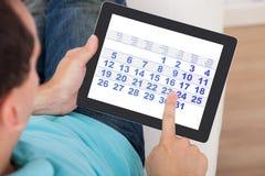 Homem que usa o calendário na tabuleta digital Imagem de Stock Royalty Free