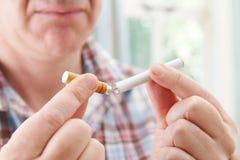 Homem que usa o cigarro eletrônico para parar de fumar imagens de stock
