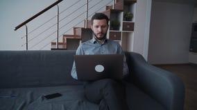 Homem que usa o computador do PC e sentando-se em casa video estoque