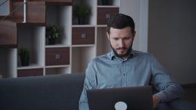 Homem que usa o computador moderno e trabalhando em casa filme