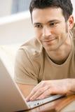 Homem que usa o computador portátil em casa Imagem de Stock Royalty Free