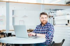 Homem que usa o laptop na cafetaria Fotos de Stock Royalty Free