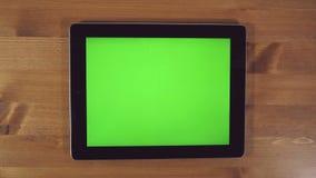 Homem que usa o PC da tabuleta com tela verde video estoque