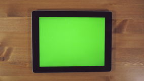 Homem que usa o PC da tabuleta com tela verde vídeos de arquivo