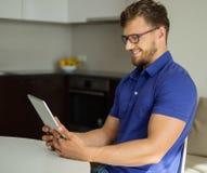 Homem que usa o PC da tabuleta em casa Imagens de Stock