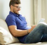 Homem que usa o PC da tabuleta em casa Imagem de Stock