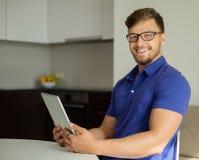 Homem que usa o PC da tabuleta em casa Fotos de Stock