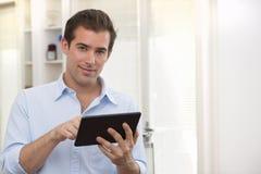 Homem que usa o PC da tabuleta interno Imagens de Stock Royalty Free