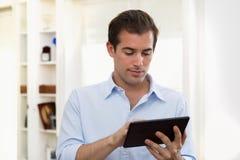 Homem que usa o PC da tabuleta interno Fotografia de Stock Royalty Free