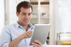 Homem que usa o PC da tabuleta no sofá em casa Imagem de Stock Royalty Free