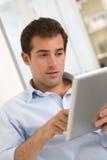 Homem que usa o PC da tabuleta no sofá em casa Imagens de Stock Royalty Free