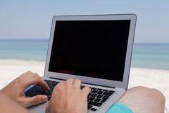 Homem que usa o portátil ao descansar na praia foto de stock