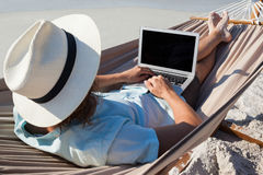 Homem que usa o portátil ao relaxar na rede imagem de stock