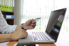 Homem que usa o portátil e as mãos que guardam o cartão de crédito, conceito em linha do pagamento foto de stock