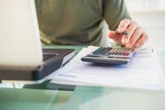 Homem que usa o portátil e a calculadora Fotografia de Stock Royalty Free