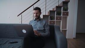 Homem que usa o portátil e passando o tempo livre em casa filme