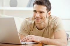 Homem que usa o portátil em casa