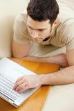 Homem que usa o portátil em casa Fotografia de Stock