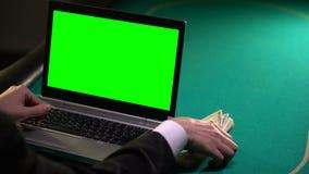 Homem que usa o portátil na tabela do pôquer, ganhando o dinheiro na aposta em linha, jogando video estoque