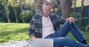 Homem que usa o portátil no jardim 4k vídeos de arquivo