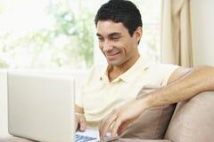Homem que usa o portátil em casa Fotografia de Stock Royalty Free