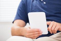 Homem que usa o smartphone em casa Foto de Stock Royalty Free