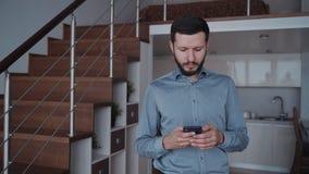 Homem que usa o smartphone moderno e enviando a mensagem em casa filme