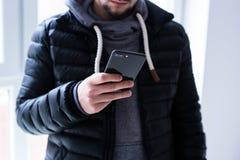 Homem que usa o smartphone no interior home imagens de stock
