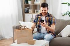 Homem que usa o smartphone para a entrega do alimento imagem de stock