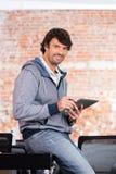 Homem que usa o sorriso ocasional do homem de negócios do tablet pc imagem de stock royalty free