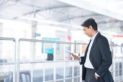 Homem que usa o tablet pc na estação de trem Imagens de Stock Royalty Free