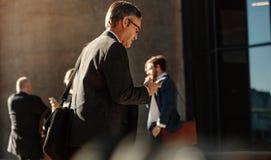 Homem que usa o telefone celular ao andar ao escritório imagens de stock