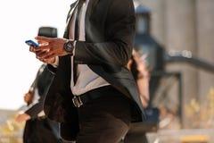 Homem que usa o telefone celular ao andar na rua imagens de stock royalty free