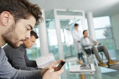 Homem que usa o telefone celular ao esperar na clínica imagens de stock royalty free