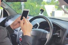 Homem que usa o telefone esperto móvel, mensagem de datilografia ou verificando o newsfeed em redes sociais no carro fotos de stock royalty free