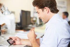Homem que usa o telefone móvel na mesa no escritório criativo ocupado foto de stock