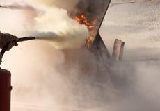 Homem que usa o tipo fogo de combate p ascendente próximo do pó do extintor imagens de stock